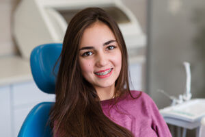 Teen with braces smiles in dentistry.
